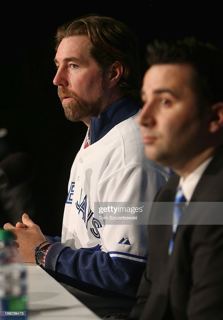 R.A. Dickey #43 of the Toronto Blue Jays listens to a question from a reporter as he is introduced at a press conference next to general manager Alex Anthopoulos at Rogers Centre on January 8, 2013 in Toronto, Ontario, Canada.