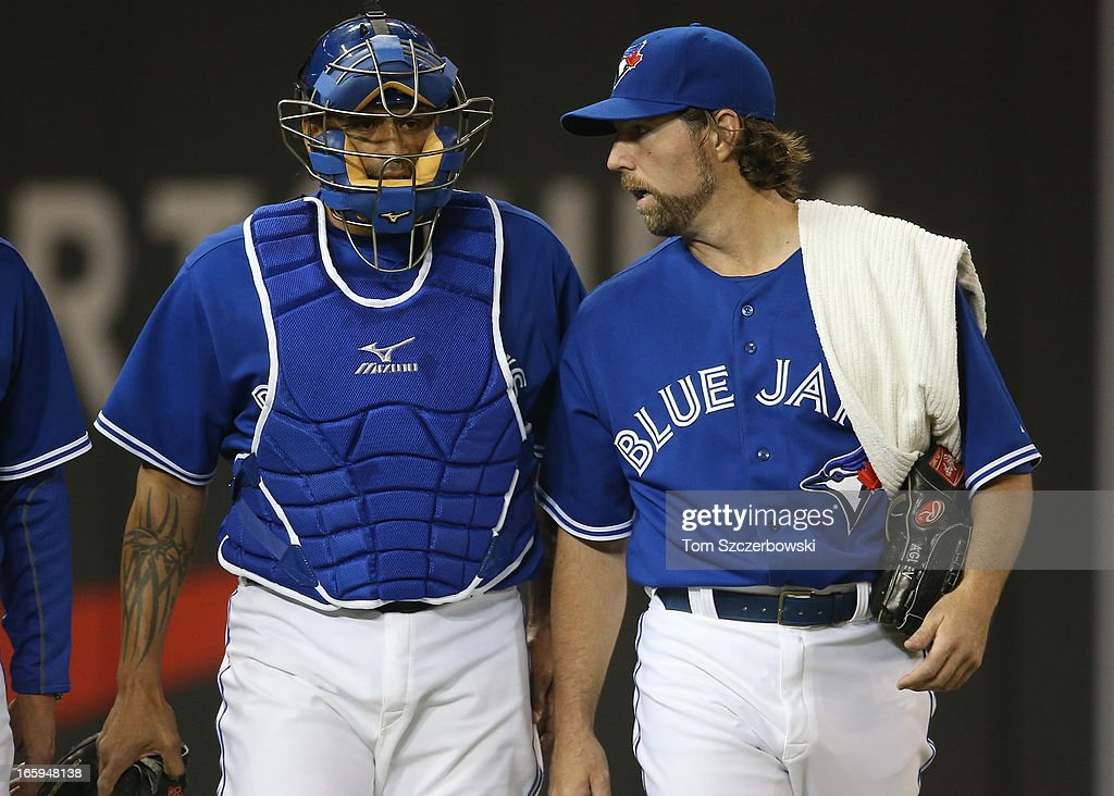 R.A. Dickey #43 of the Toronto Blue Jays makes his way from the bullpen to the dugout with Henry Blanco #22 before the start of MLB game action against the Boston Red Sox on April 7, 2013 at Rogers Centre in Toronto, Ontario, Canada.