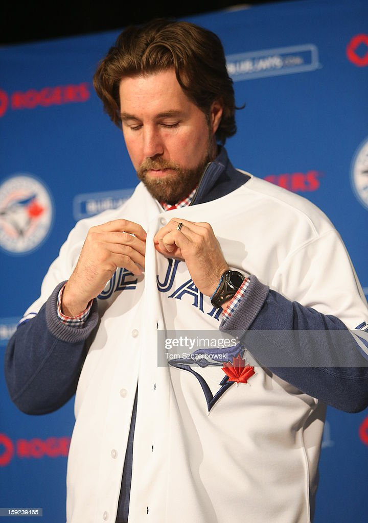 R.A. Dickey #43 of the Toronto Blue Jays puts on a Blue Jays jersey during his introduction at a press conference at Rogers Centre on January 8, 2013 in Toronto, Ontario, Canada.