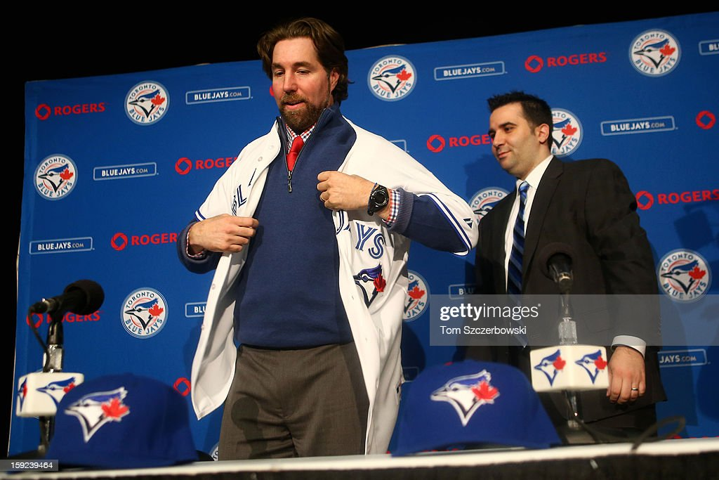 R.A. Dickey #43 of the Toronto Blue Jays puts on his jersey as he is introduced at a press conference by general manager Alex Anthopoulos at Rogers Centre on January 8, 2013 in Toronto, Ontario, Canada.