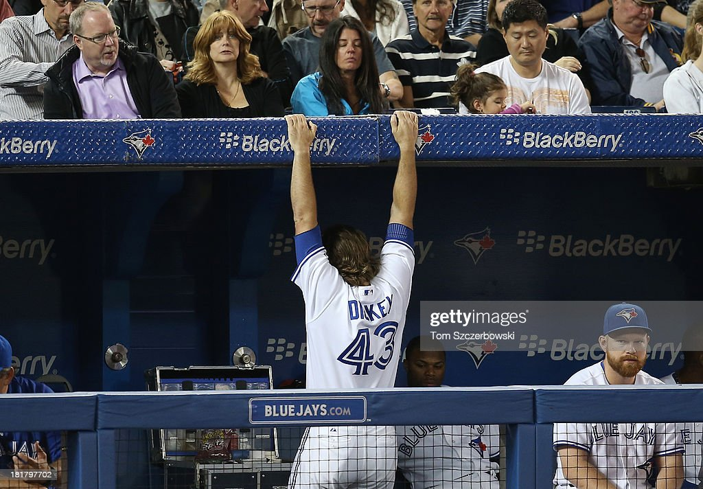R.A. Dickey #43 of the Toronto Blue Jays stretches between innings by suspending himself from the dugout roof during MLB game action against the New York Yankees on September 17, 2013 at Rogers Centre in Toronto, Ontario, Canada.
