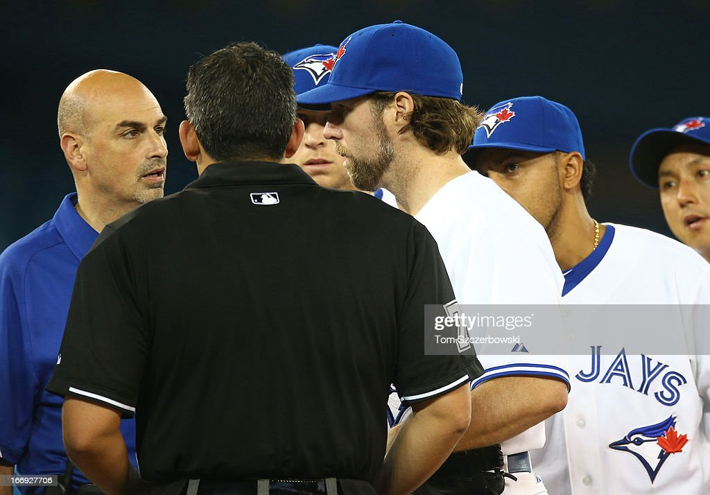 R.A. Dickey #43 of the Toronto Blue Jays talks to trainer George Poulis as he left the game due to injury in the seventh inning during MLB game action against the Chicago White Sox on April 18, 2013 at Rogers Centre in Toronto, Ontario, Canada.