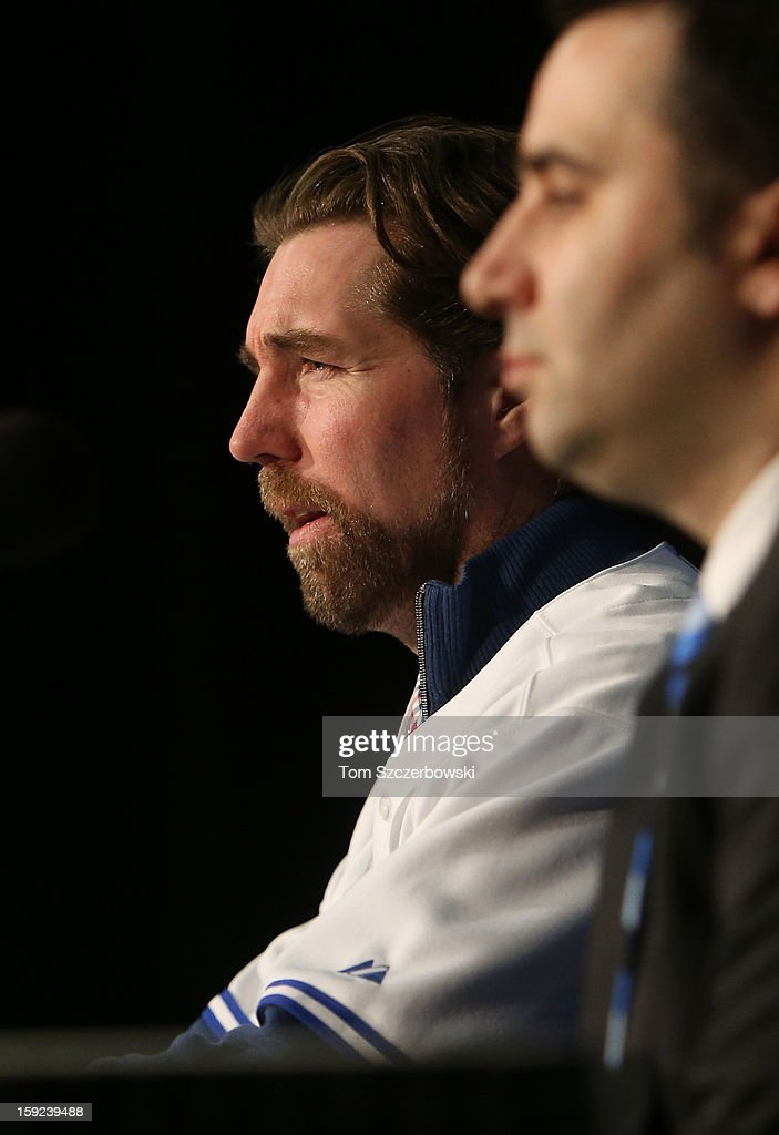 R.A. Dickey #43 of the Toronto Blue Jays tells reporters about his sexual abuse as he is introduced at a press conference next to general manager Alex Anthopoulos at Rogers Centre on January 8, 2013 in Toronto, Ontario, Canada.
