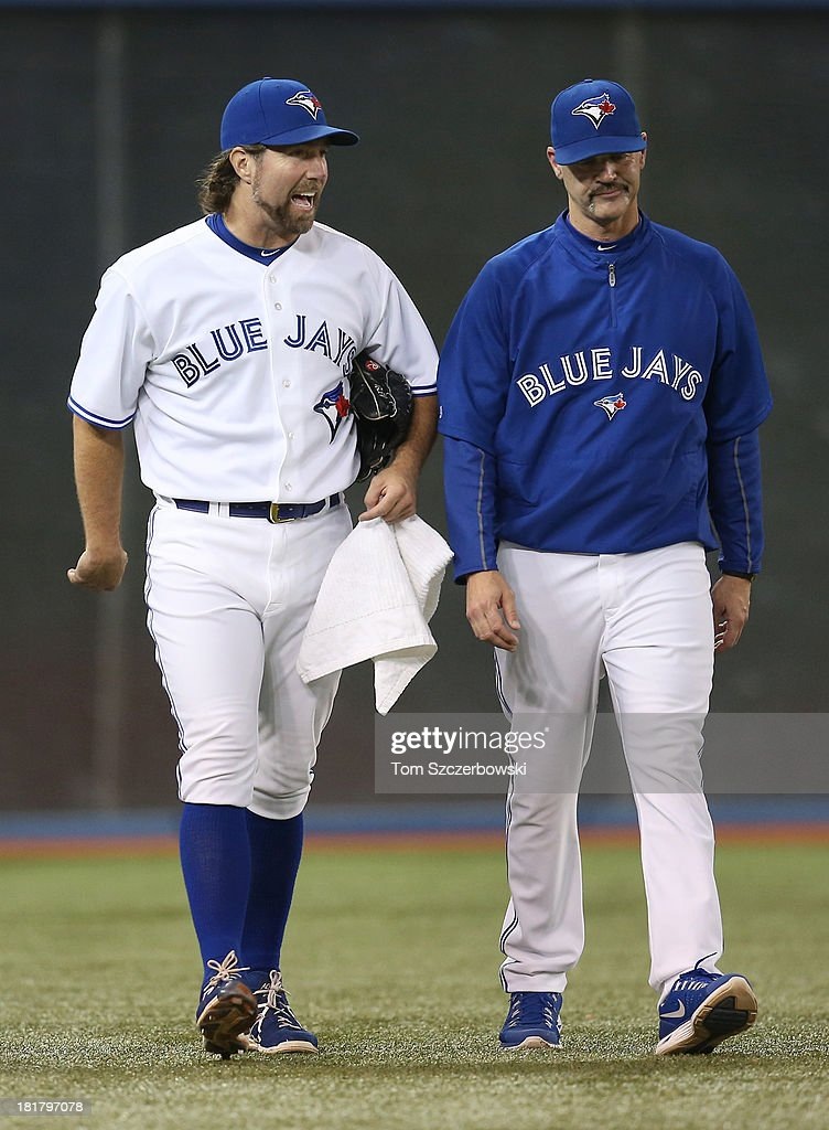 R.A. Dickey #43 of the Toronto Blue Jays walks from the bullpen to the dugout with pitching coach Pete Walker #40 before the start of MLB game action against the New York Yankees on September 17, 2013 at Rogers Centre in Toronto, Ontario, Canada.