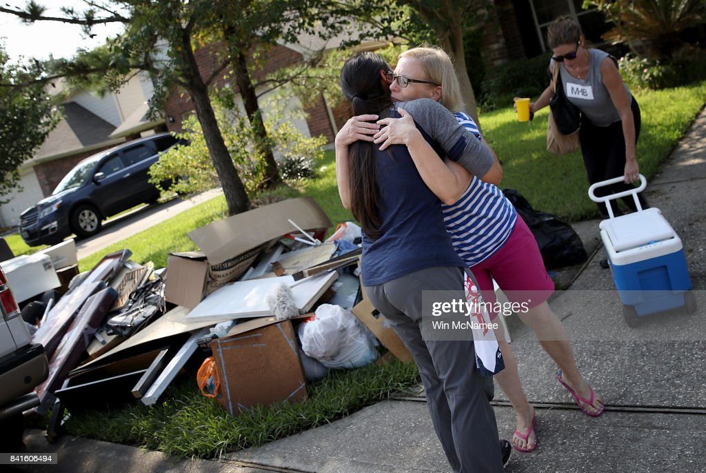 A Dickinson resident hugs a friend who came to help her remove possessions damaged by flooding brought on by Hurricane Harvey September 1, 2017 in Dickinson, Texas. Dickinson was hit by Hurricane Harvey extremely hard with major flooding in many areas of the city and residents there are beginning the long process of recovering from the storm.