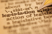 Legislation pen nib pointing to the words in the dictionary, shot with very shallow depth of field,