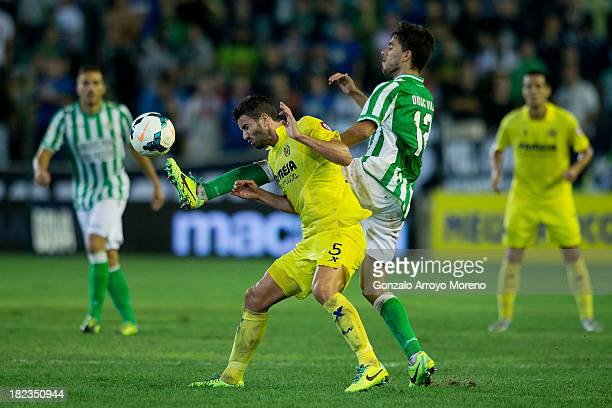 Didac Vila of Real Betis Balompie competes for the ball with Mateo Pablo Musacchio of Villarreal CF during the La Liga match between Real Betis...