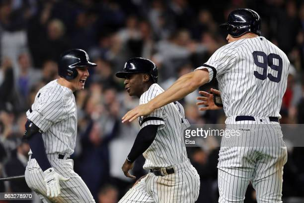 Didi Gregorius and Aaron Judge of the New York Yankees celebrate with teammate Greg Bird after scoring in the eighth inning against the Houston...