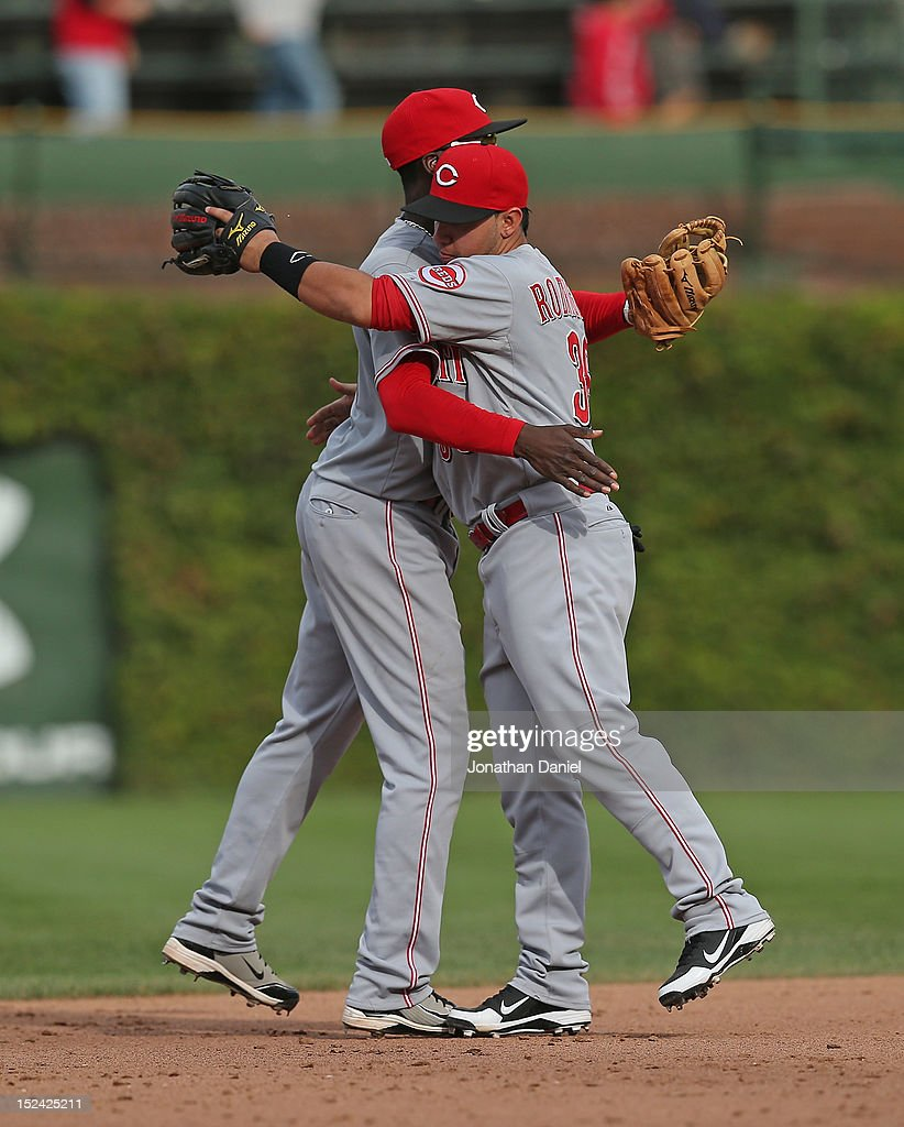 Didi Gregorius #25 (L) and Henry Rodriguez #36 of the Cincinnati Reds hug after a win over the Chicago Cubs at Wrigley Field on September 20, 2012 in Chicago, Illinois. The Reds defeated the Cubs 5-3.