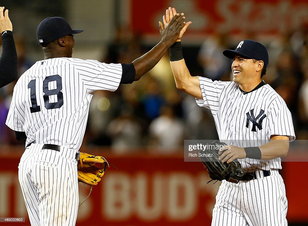 Didi Gregorius #18 high fives Jacoby Ellsbury #22 of the New York Yankees after the final out in the ninth inning against the Boston Red Sox during a MLB baseball game at Yankee Stadium on August 6, 2015 in the Bronx borough of New York City. The Yankees defeated the Red Sox 2-1.