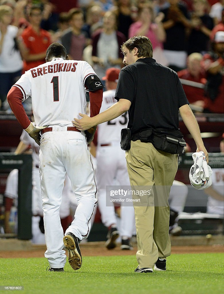 Didi Gregorius #1 of the Arizona Diamondbacks is escorted back to the dugout after being hit in the head by a pitch from Josh Outman (not pictured) of the Colorado Rockies in the seventh inning at Chase Field on April 26, 2013 in Phoenix, Arizona.