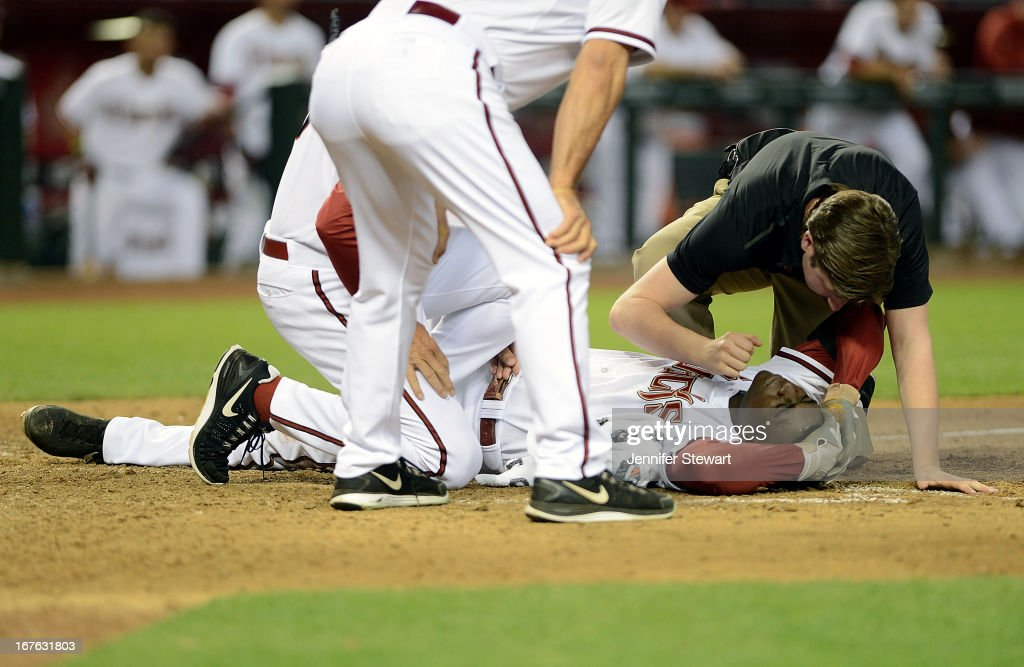 Didi Gregorius #1 of the Arizona Diamondbacks is examined by a member of the medical staff after being hit in the head by a pitch from Josh Outman (not pictured) of the Colorado Rockies in the seventh inning at Chase Field on April 26, 2013 in Phoenix, Arizona.