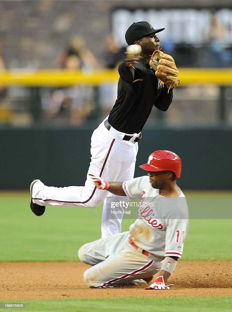 Didi Gregorius #1 of the Arizona Diamondbacks turns a double play as <a gi-track='captionPersonalityLinkClicked' href=/galleries/search?phrase=Jimmy+Rollins&family=editorial&specificpeople=204478 ng-click='$event.stopPropagation()'>Jimmy Rollins</a> #11 of the Philadelphia Phillies slides into second base at Chase Field on May 11, 2013 in Phoenix, Arizona.