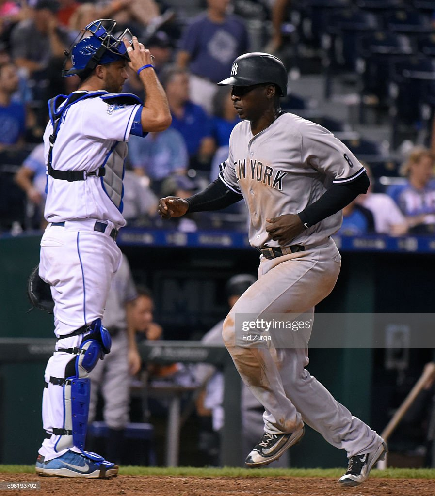 Didi Gregorius #18 of the New York Yankees crosses home past Drew Butera #9 of the Kansas City Royals as he scores on a Brian McCann #34 sacrifice fly in the 13th inning at Kauffman Stadium on August 31, 2016 in Kansas City, Missouri.