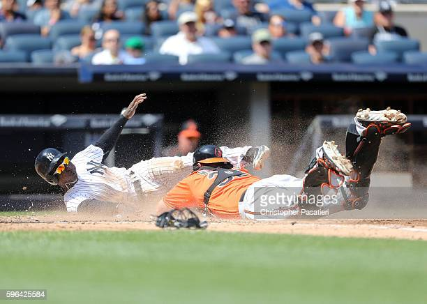 Didi Gregorius of the New York Yankees dives for home plate past catcher Matt Wieters of the Baltimore Orioles to score in the bottom of the third...