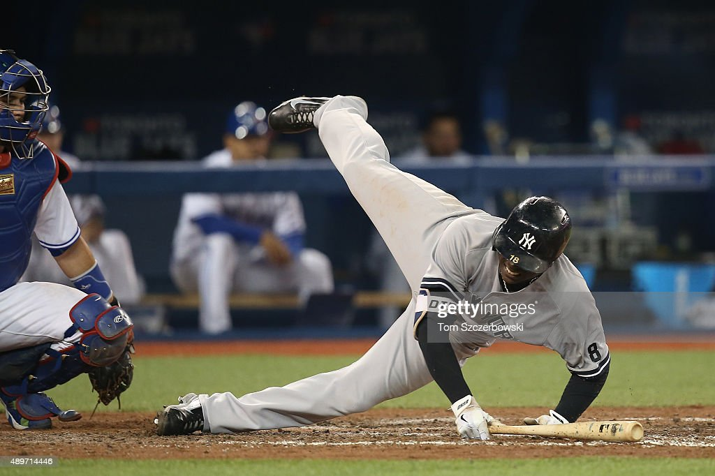 Didi Gregorius #18 of the New York Yankees falls after fouling a ball off his foot in the eighth inning during MLB game action against the Toronto Blue Jays on September 23, 2015 at Rogers Centre in Toronto, Ontario, Canada.