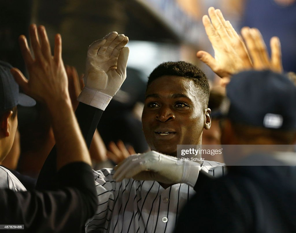 Didi Gregorius #18 of the New York Yankees is congratulated by teammates after he hit a three run home run in the sixth inning against the Toronto Blue Jays during a MLB baseball game at Yankee Stadium on September 11, 2015 in the Bronx borough of New York City.