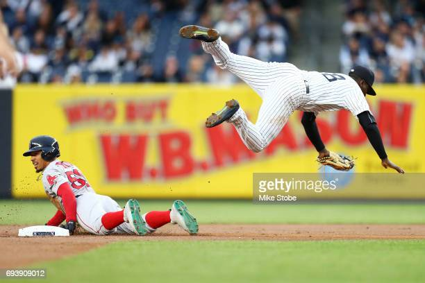 Didi Gregorius of the New York Yankees is tripped up after tagging out Mookie Betts of the Boston Red Sox trying to steal second base in the first...