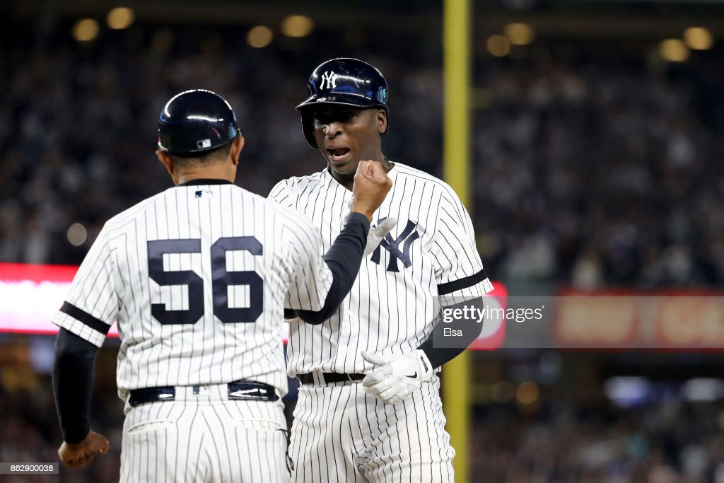 Didi Gregorius #18 of the New York Yankees reacts with first base coach Tony Pena #56 after hitting a single scoring Aaron Judge #99 during the fifth inning against the Houston Astros in Game Five of the American League Championship Series at Yankee Stadium on October 18, 2017 in the Bronx borough of New York City.