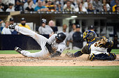 Didi Gregorius of the New York Yankees scores ahead of the tag of Derek Norris of the San Diego Padres during the second inning of a baseball game at...