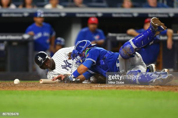 Didi Gregorius of the New York Yankees slides in saftley as Luke Maile of the Toronto Blue Jays is unable to handle the throw in the eighth inning at...