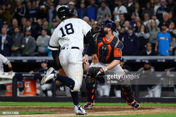 Didi Gregorius of the New York Yankees slides in to home after tagging up on a fly out by Gary Sanchez as catcher Brian McCann of the Houston Astros...