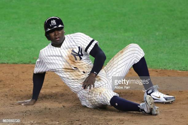Didi Gregorius of the New York Yankees slides in to home after tagging up on a sacrifice fly by Gary Sanchez during the seventh inning against the...