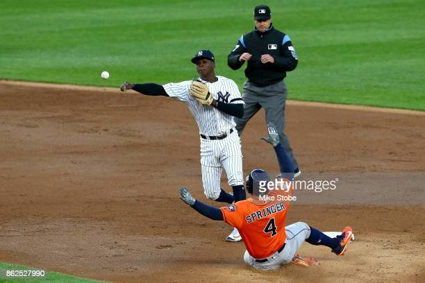 Didi Gregorius of the New York Yankees throws to first to finish a double play during the third inning as George Springer of the Houston Astros...