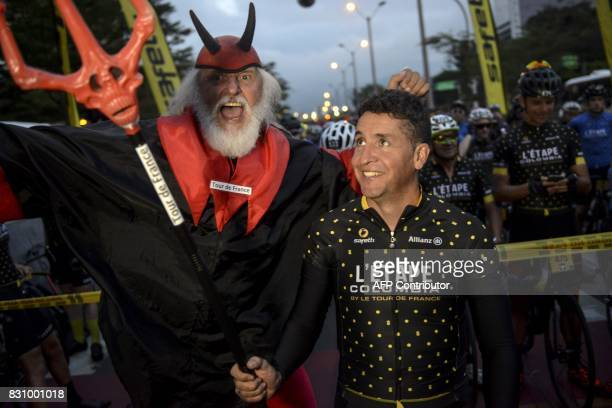 'Didi the Devil' and former professional cyclist and 2008 Tour de France champion Spaniard Carlos Sastre are pictured before the start of 'L'Etape...