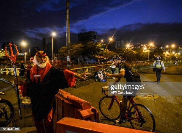 Didi the Devil salutes an amateur cyclist before the start of 'L'Etape Colombia by Le Tour de France' in Medellin Colombia on August 13 2017 / AFP...