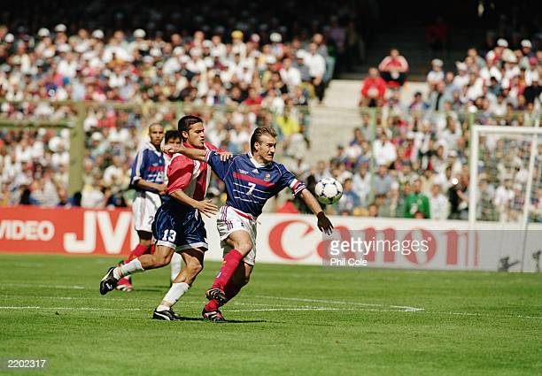Didier Deschamps of France is held back by Carlos Paredes of Paraguay during the FIFA World Cup Finals 1998 Second Round match between France and...