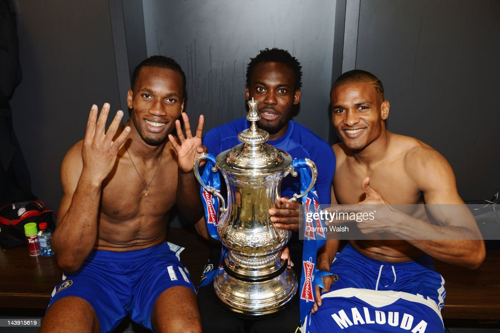 (L-R)Didier Drogba, Michael Essien and FLorent Malouda of Chelsea celebrate with the trophy in the changing room after the FA Cup Final with Budweiser between Liverpool and Chelsea at Wembley Stadium on May 5, 2012 in London, England.