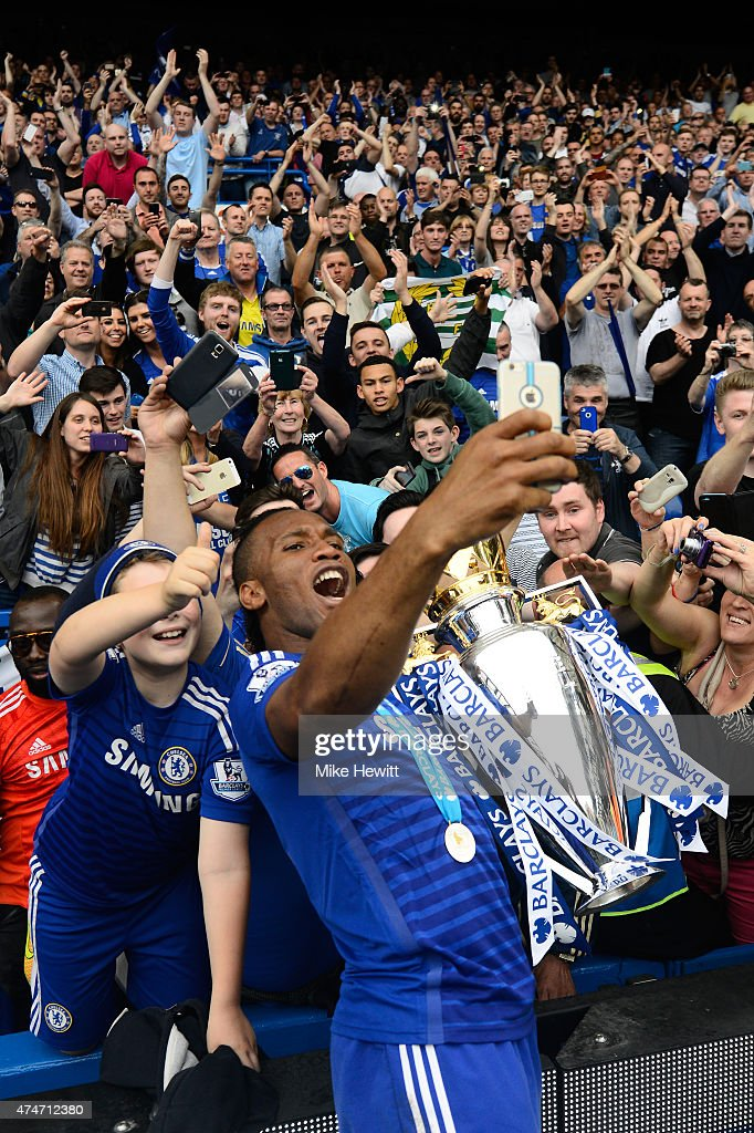 Didier Drogba of Chelsea celebrates with fans and the trophy after the Barclays Premier League match between Chelsea and Sunderland at Stamford Bridge on May 24, 2015 in London, England. Chelsea were crowned Premier League champions.