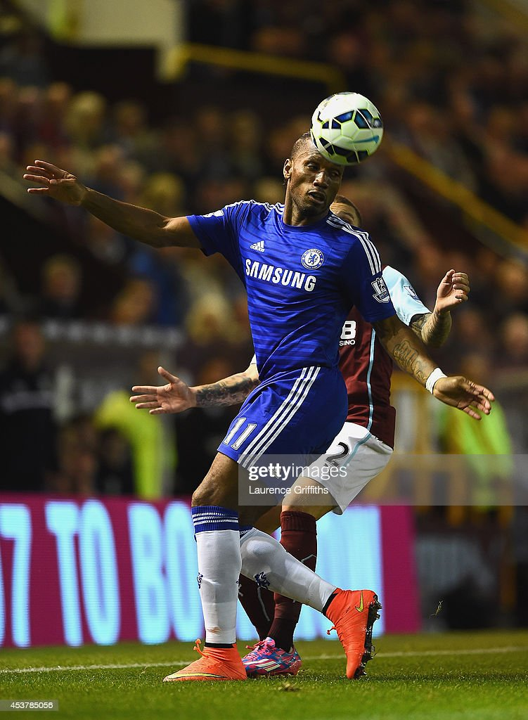 Didier Drogba of Chelsea controls the ball under pressure from Kieran Trippier of Burnley during the Barclays Premier League match between Burnley and Chelsea at Turf Moor on August 18, 2014 in Burnley, England.