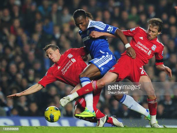 Didier Drogba of Chelsea is tackled by Lucas and Daniel Agger of Liverpool during the Barclays Premier League match between Chelsea and Liverpool at...