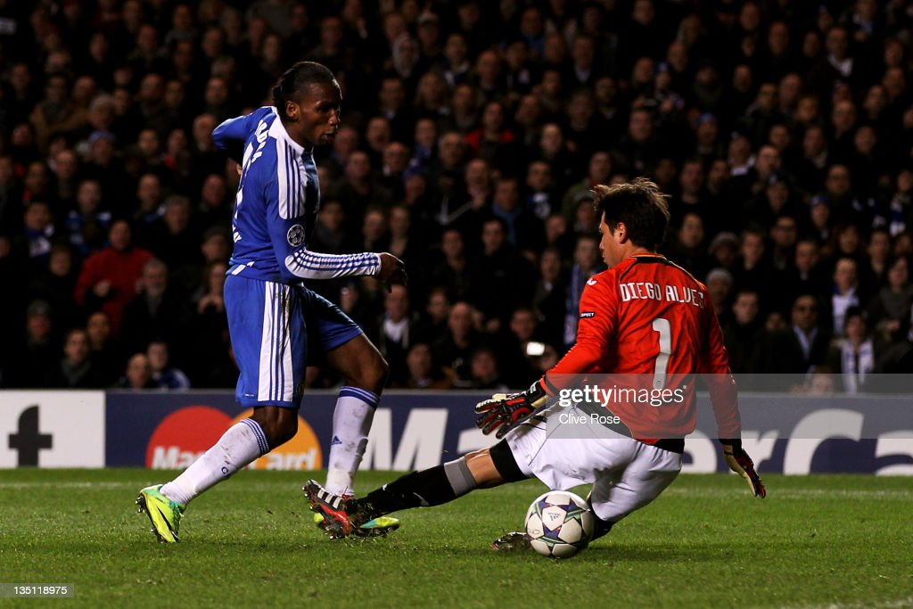 Didier Drogba of Chelsea slips the ball past goalkeeper Diego Alves of Valencia to score his team's third goal during the UEFA Champions League group E match between Chelsea FC and Valencia CF at Stamford Bridge on December 6, 2011 in London, England.