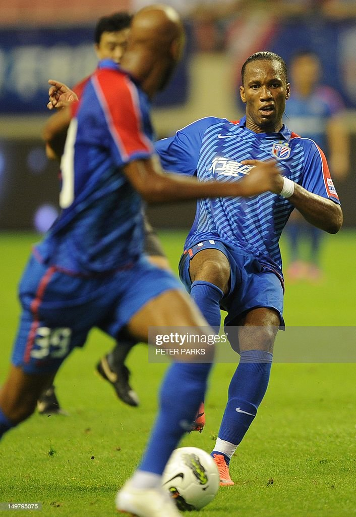 Didier Drogba (R) passes to teammate Nicolas Anelka (L) as they play for Shanghai Shenhua FC in their game against Hangzhou Greentown in Shanghai on August 4, 2012. AFP PHOTO/Peter PARKS