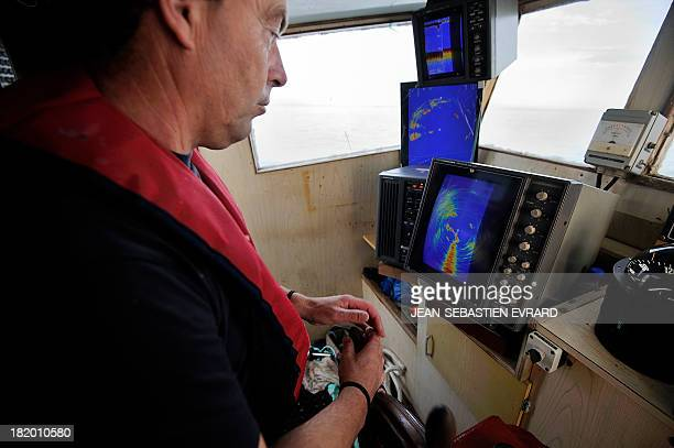 Didier Jacob captain of the fishing boat 'Kanedevenn' observes the sonar as he sails in search of sardines on September 24 2013 in Quiberon western...