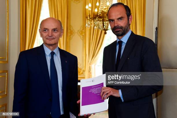 Didier Migaud president of the Court of Auditors and French Prime Minister Edouard Philippe pose with a audit report on public finances at the Hotel...