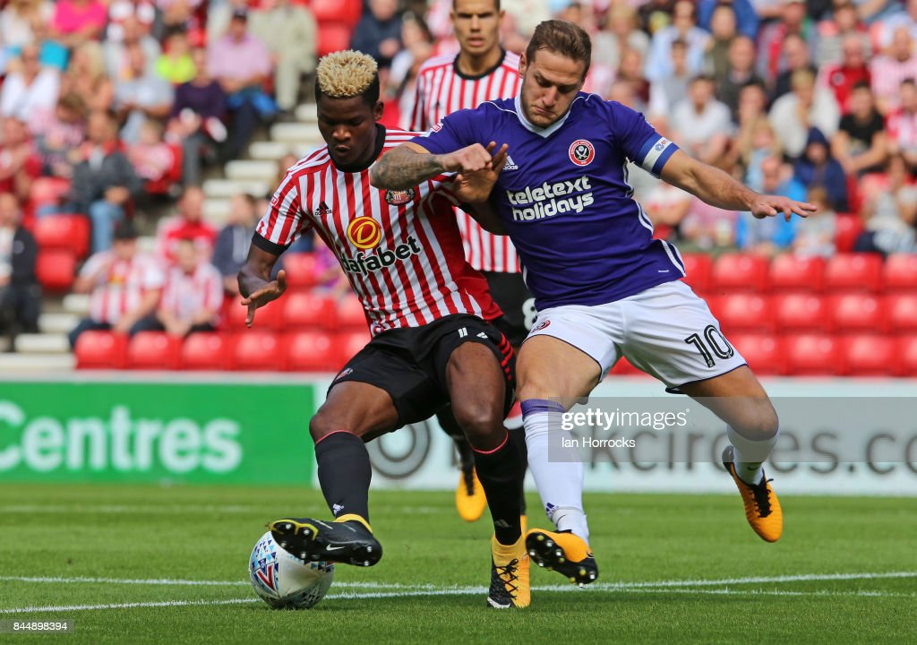 Didier N'Dong of Sunderland (L) under pressure from Billy Sharp of Sheffield during the Sky Bet Championship match between Sunderland and Sheffield United at Stadium of Light on September 9, 2017 in Sunderland, England.
