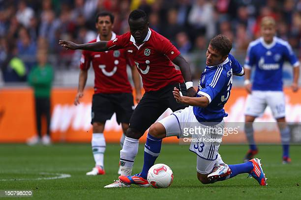 Didier Ya Konan of Hannover challenges Roman Neustaedter of Schalke during the Bundesliga match between Hannover 96 and FC Schalke 04 at AWD Arena on...