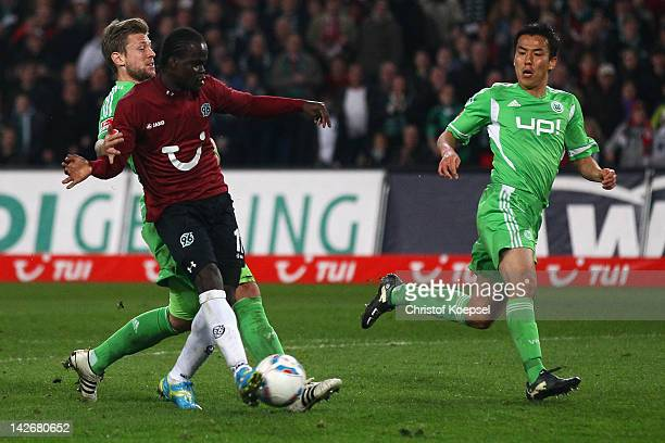 Didier Ya Konan of Hannover scores the second goal against Marco Russ of Wolfsburg and Makoto Hasebe of Wolfsburg during the Bundesliga match between...