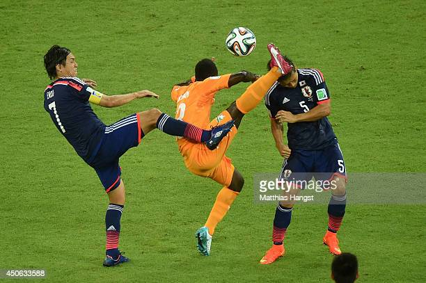 Didier Ya Konan of the Ivory Coast competes for the ball with Yasuhito Endo and Yuto Nagatomo of Japan during the 2014 FIFA World Cup Brazil Group C...