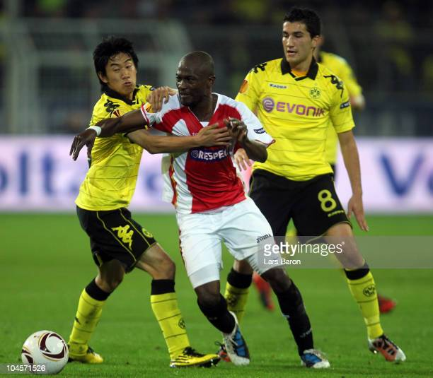 Didier Zokora of Sevilla is challenged by Shinji Kagawa and Nuri Sahin of Dortmund during the UEFA Europa League group J match between Borussia...