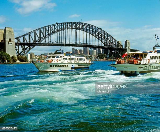 Die beruehmte Hafenbruecke ist eines der Wahrzeichen von Sydney davor Ausflugsboote und Faehren im Naturhafen der Sydney Cove in Australien