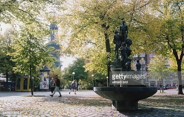 Die Bäume rund um den Brunnen auf dem Großneumarkt verlieren ihr Laub Aus dem Brunnen heraus ragt eine Steintreppe auf der mehrere Bronzefiguren und...