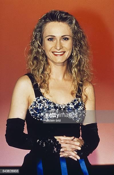Die deutsche Schlagersängerin Nicole in einem Abendkleid dessen Brustpartie mit Steinen besetzt ist dazu trägt sie Halbhandschuhe Sie hält die Hände...