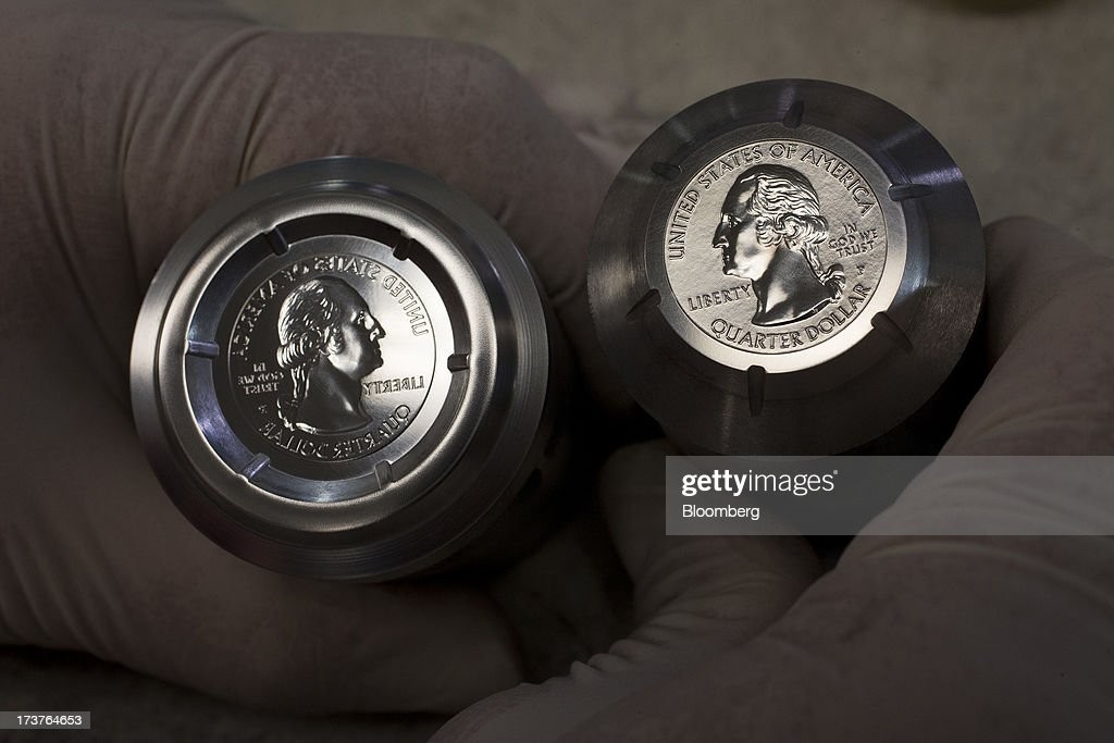 A die to be used for pressing U.S. quarter dollars, left, is displayed for a photograph next to a hub at the U.S. Mint in Philadelphia, Pennsylvania, U.S., on Wednesday, July 17, 2013. Some sources of declining inflation 'are likely to be transitory' and expectations for future price increases 'have generally remained stable,' Ben S. Bernanke, chairman of the U.S. Federal Reserve said in prepared remarks. Photographer: Scott Eells/Bloomberg via Getty Images