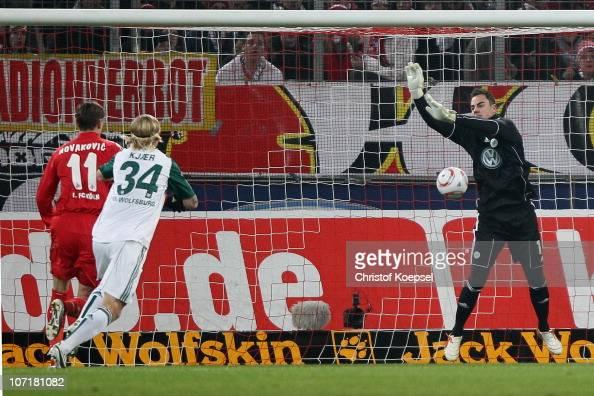 Diego Benaglio of Wolfsburg drops the ball against Milivoje Novakovic of Koeln Patrick Helmes of Leverkusen who scores the fiorst goal during the...