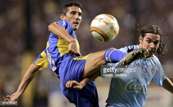 Diego Cagna of Boca Juniors of Argentina and Ruben Tufino of Bolivar of La Paz Bolivia vie for the ball during their final Copa Sudamericana match at...